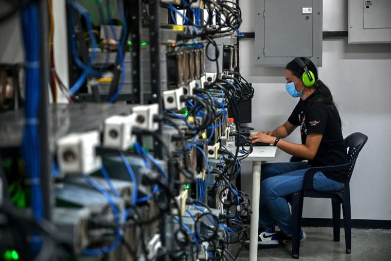 An employee inspects computers used to mine Bitcoins at the mining showroom of the Doctorminer company in Caracas on August 18, 2021. In a Venezuela with ridiculously low electricity costs, mining cryptocurrencies has become a very profitable business, albeit a target for extortion.