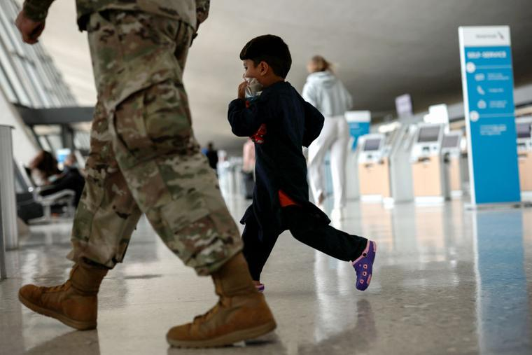 An Afghan boy walks with a U.S. service member as he and his family are led through the Dulles International Airport to board a bus that will take them to a refugee processing center after being evacuated from Kabul following the Taliban takeover of Afghanistan on August 31, 2021 in Dulles, Virginia.