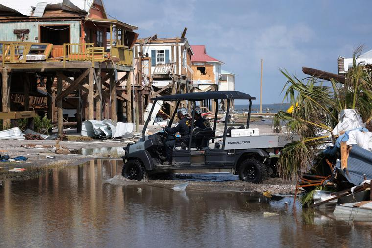 A search and rescue team drives through standing water while checking homes destroyed in the wake of Hurricane Ida on September 2, 2021 in Grand Isle, Louisiana.
