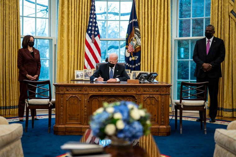 Flanked by Vice President Kamala Harris, l, and Secretary of Defense Lloyd Austin, r, U.S. President Joe Biden signs an executive order repealing the ban on transgender people serving openly in the military in the Oval Office of the White House on Jan. 25.