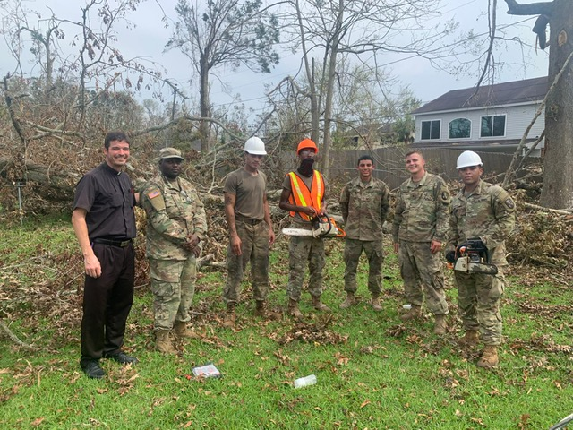 Father Steve Dardis stands with members of the National Guard from Plaquemine, Louisiana who assisted in clean up of Holy Family Parish in Luling after Hurricane Ida.