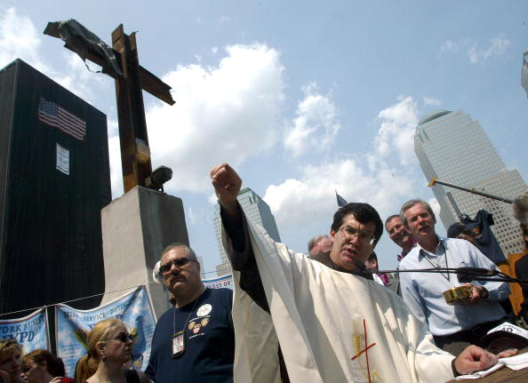 NEW YORK, UNITED STATES:  Father Brian Jordan presides over the final Sunday Mass at Ground Zero in New York, June 02, 2002. Several hundred relatives of those killed in the Sept. 11 attacks on the World Trade Center gathered for a day of interfaith services.