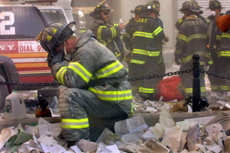 Firefighter Gerard McGibbon, of Engine 283 in Brownsville, Brooklyn, prays after the World Trade Center buildings collapsed on Sept. 11, 2001.