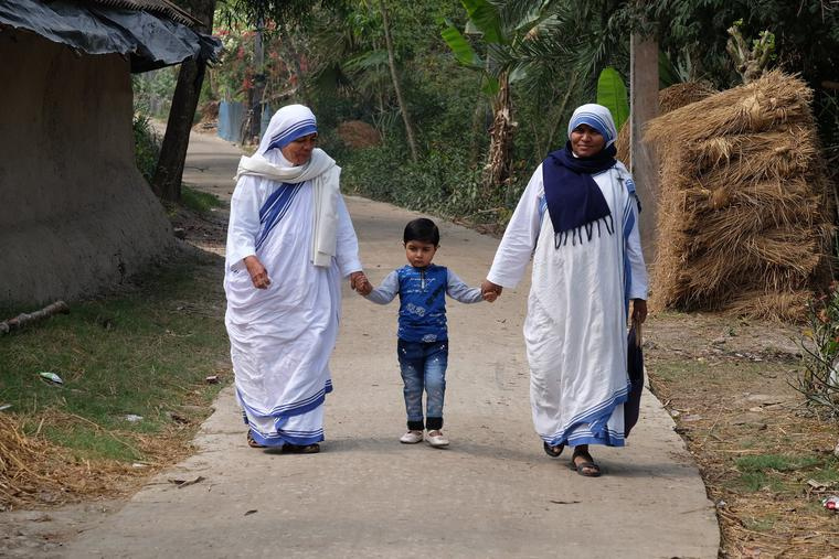Missionaries of Charity nuns walk with a child in Chunakhali, West Bengal, India, on Feb. 26, 2020.