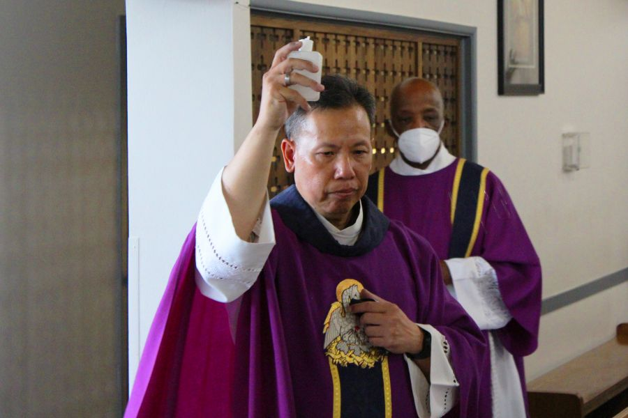 Father Joseph Cao, assisted by Deacon Clarence McDavid, blesses the parts of the church affected by an Aug. 30 break-in during a Mass of reparation at Curé d'Ars Catholic Church in Denver on Sept. 1.