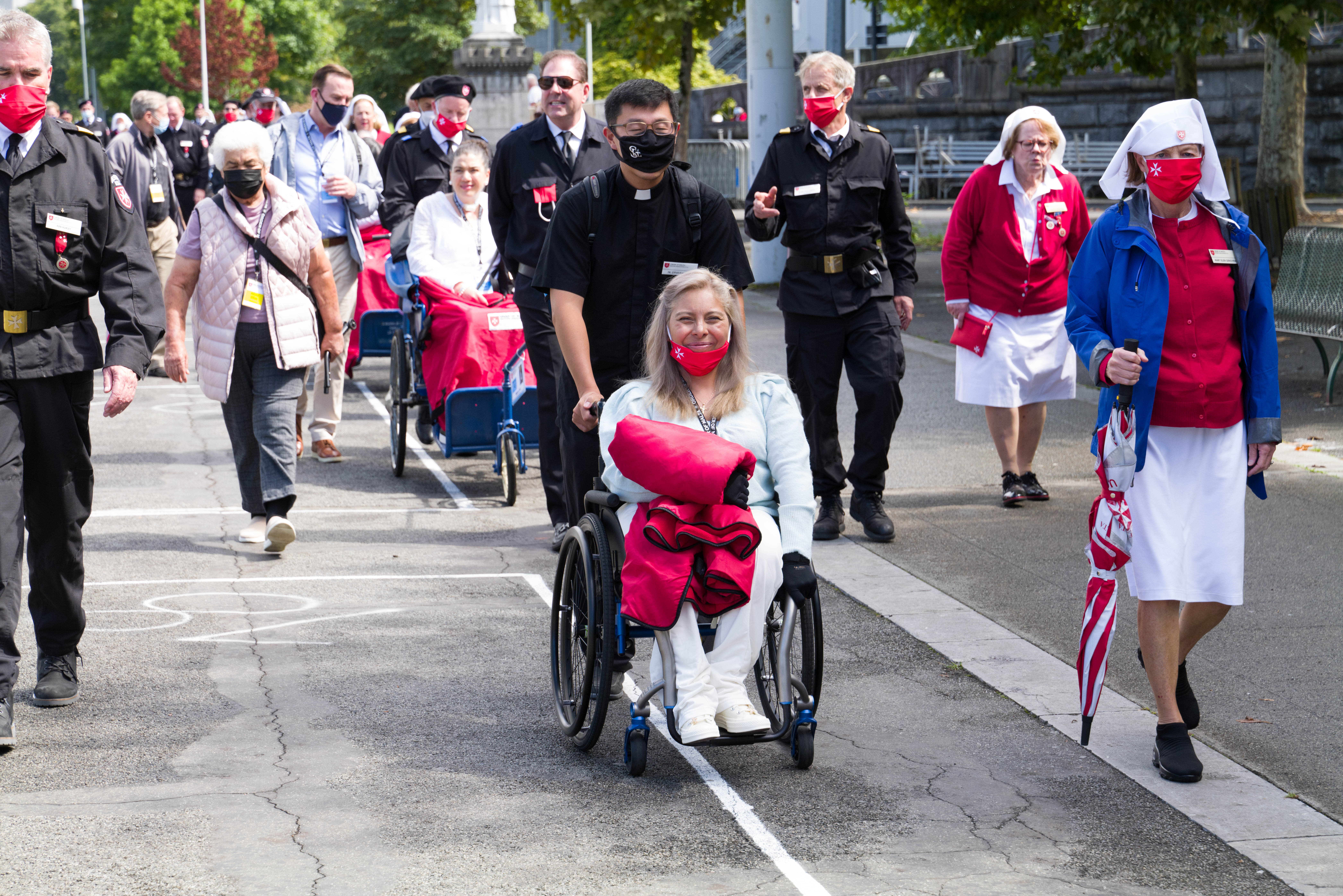 A malade makes her way Our Lady of Lourdes Shrine and Grotto accompanied by her family and members of the Order of Malta.