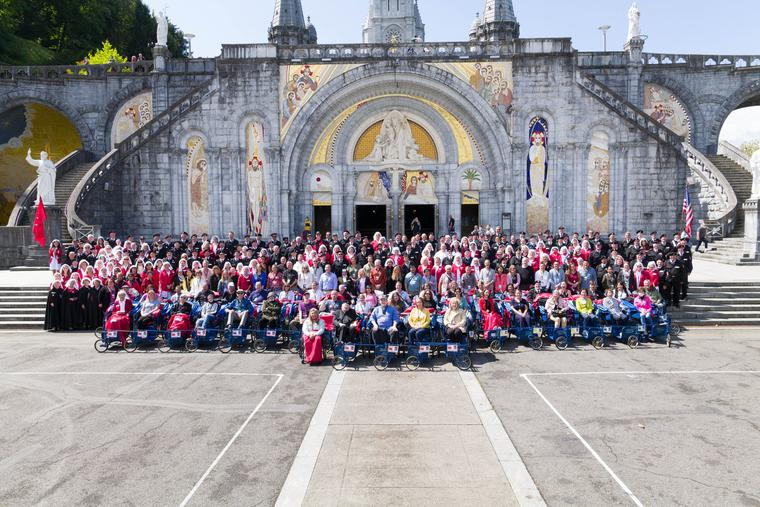 Malades and members of the Order of Malta pose for a picture in front of the Rosary Basilica.