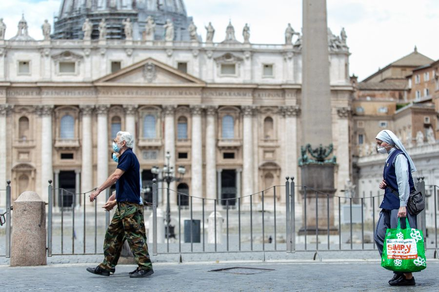 People wearing face coverings walk past St. Peter's Basilica.