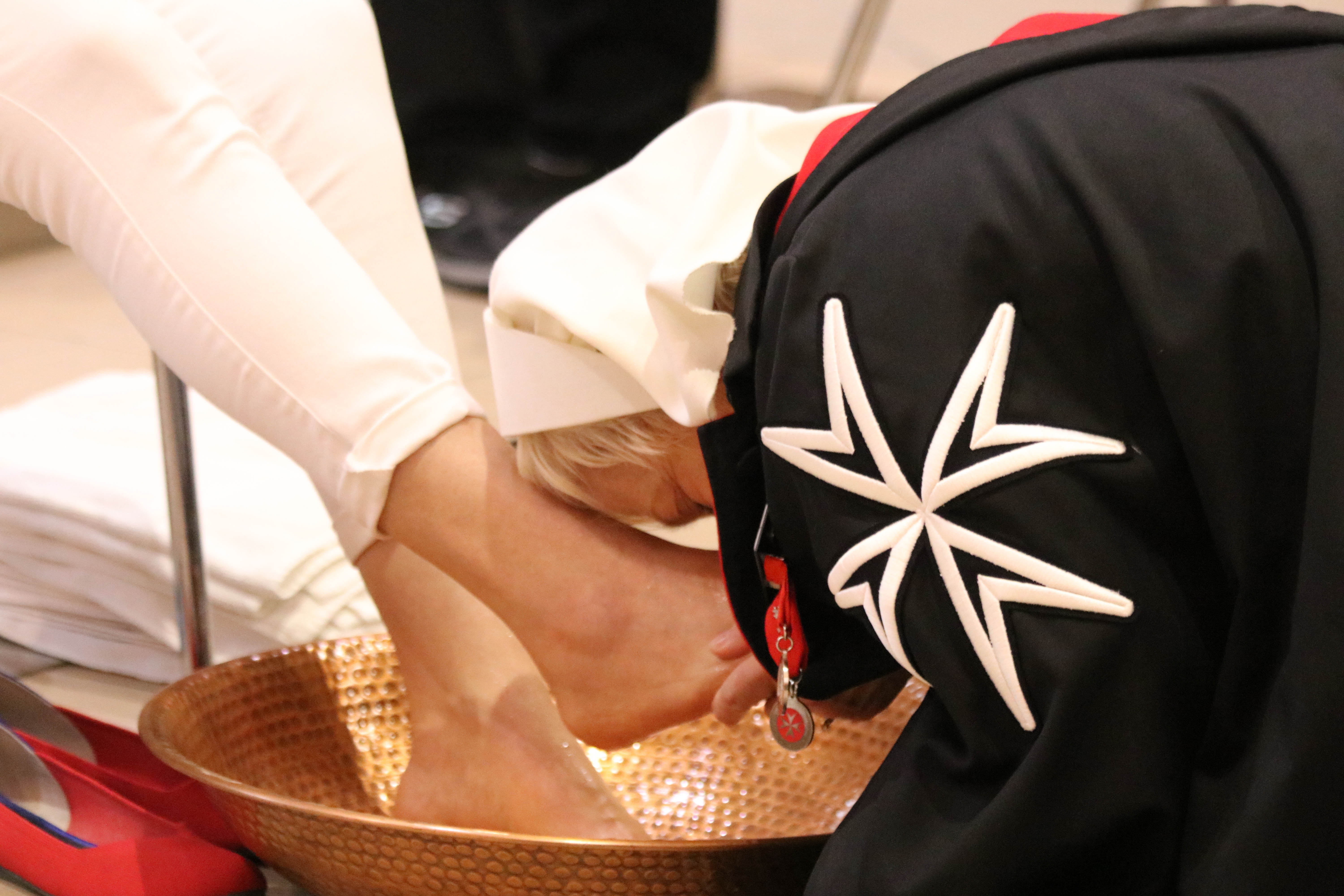 A dame of Malta washes the feet of a malade in Lourdes. courtesy