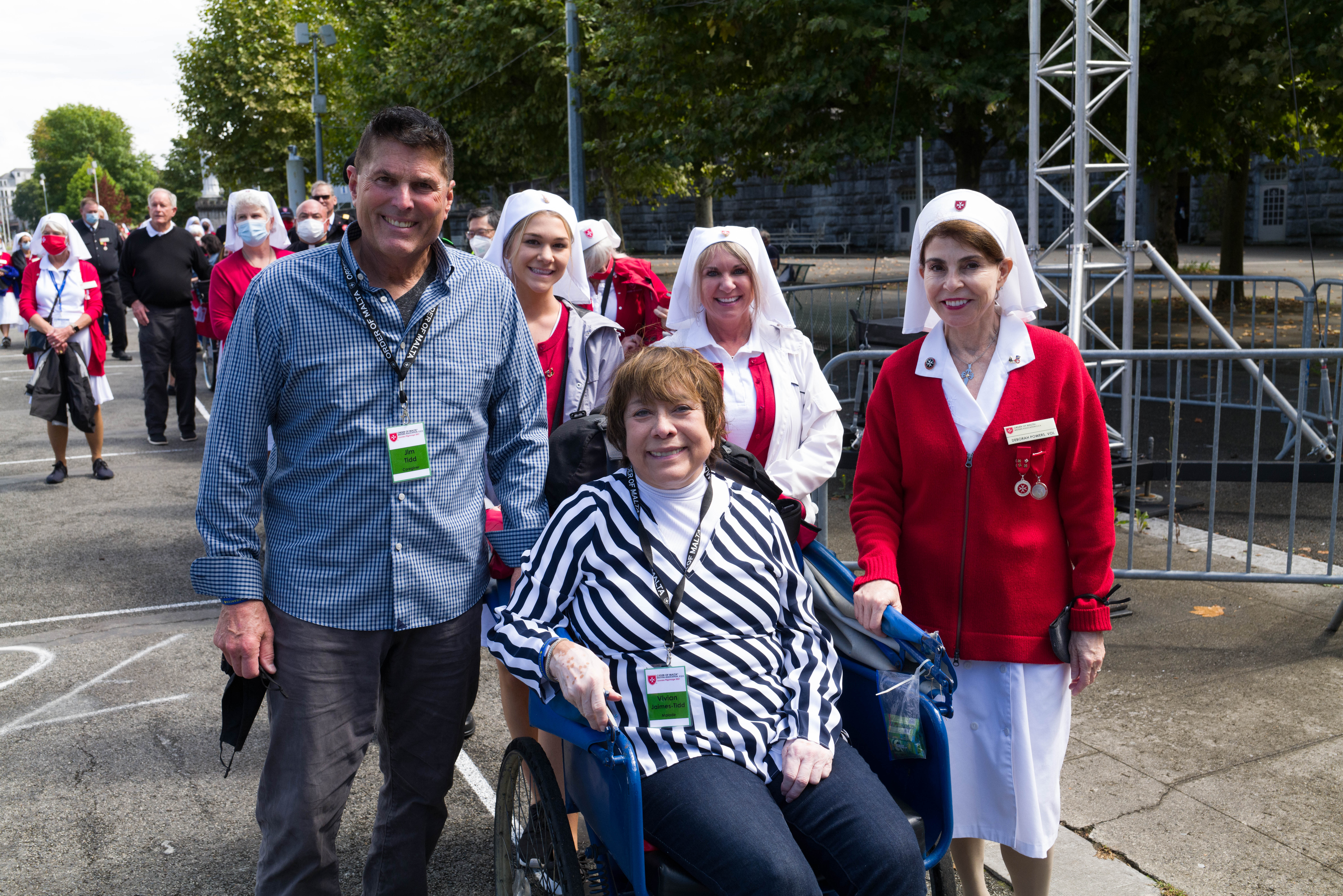Malade Vivian Jaimes-Tidd (in voiture) and her husband Jim Tidd (standing) while attending the 2021 Lourdes Pilgrimage with The Order of Malta Western Association USA (9/1/2021-9/8/2021). Also featured in the foreground in uniform (if needed) are Deborah Powers, Jacqueline Grisotti, and Emilia Grisotti. Photo credit Western Association USA of The Order of Malta.