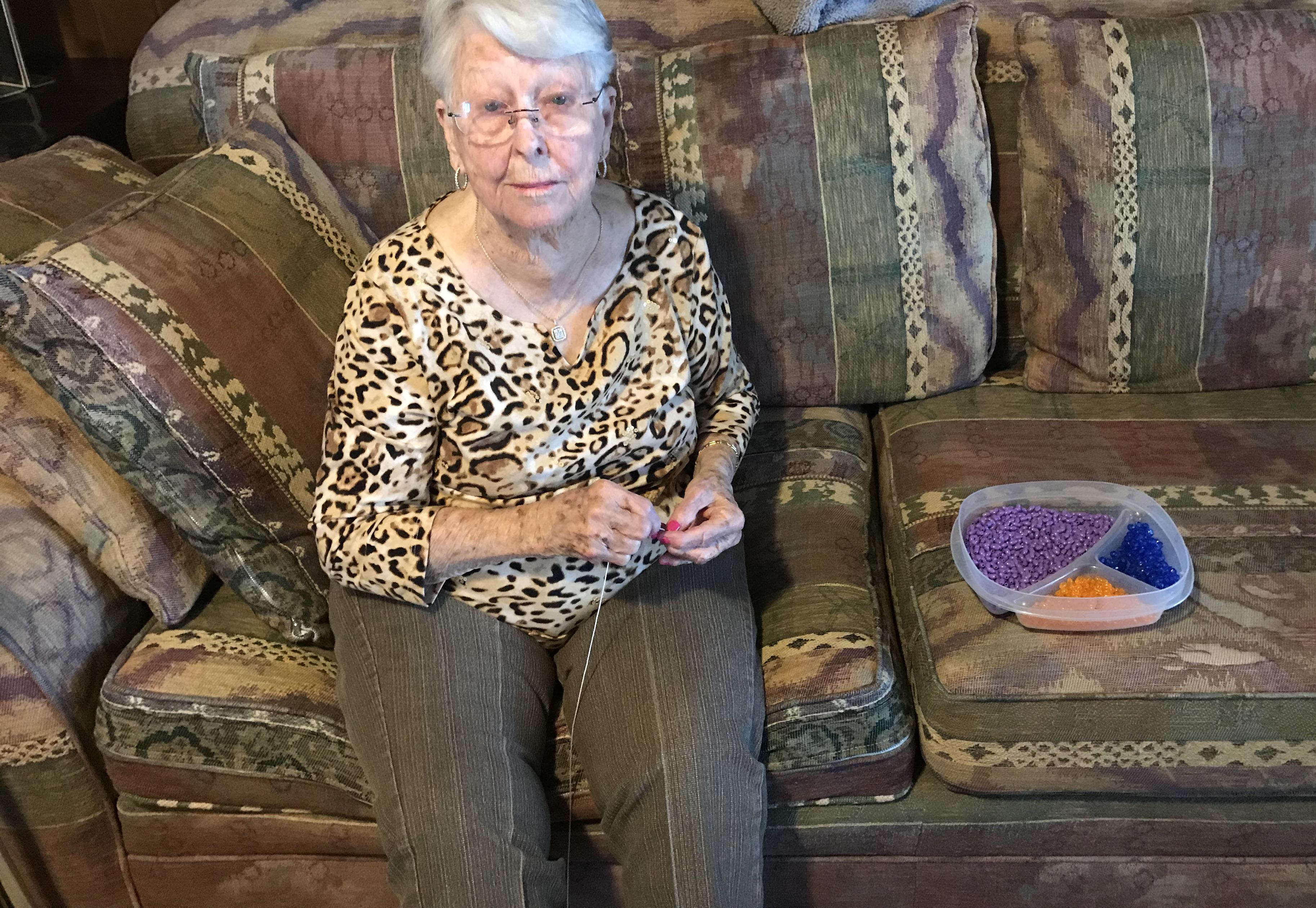 At almost 100, Clodine Norris enjoys making rosaries.
