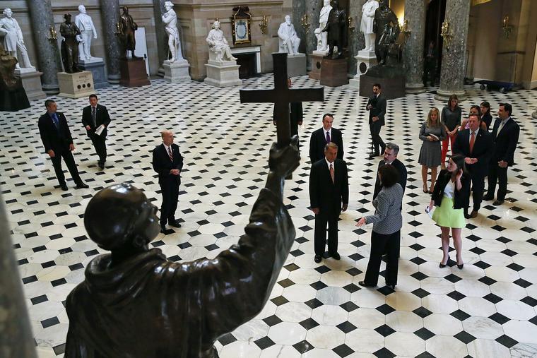 House Speaker John Boehner (R-OH) (C) walks through Statuary Hall in Washington, DC, in front of the statue of Junípero Serra on Sept. 16, 2015.