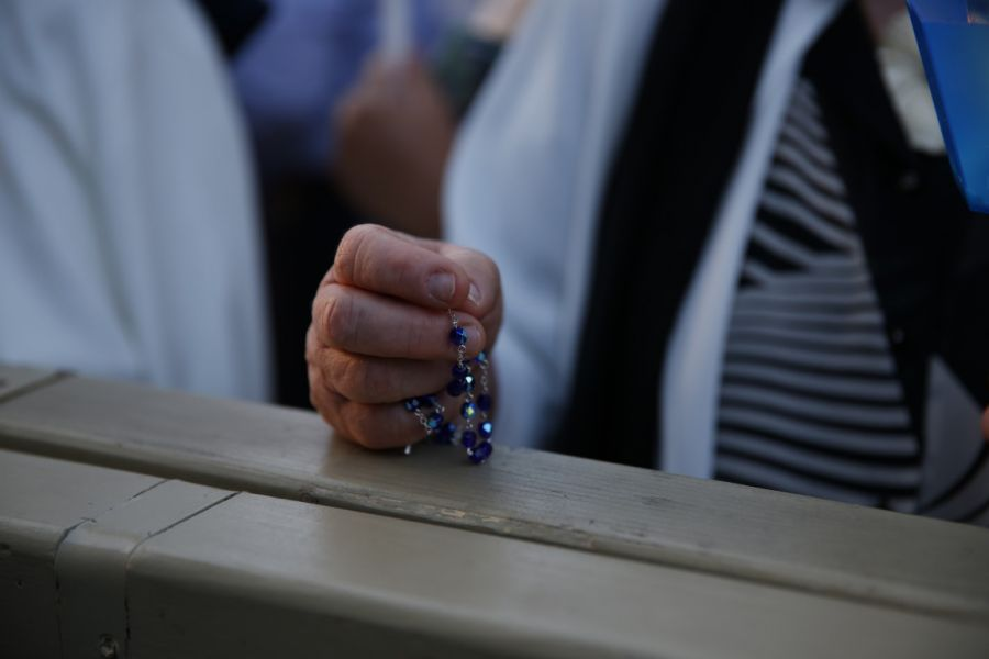 A woman holds her beads praying the Rosary.