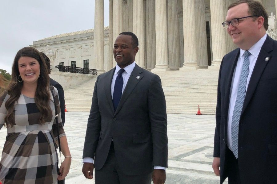 Daniel Cameron, attorney general of Kentucky (center) and his wife Makenze (left) gather with Matthew Kuhn, principal deputy solicitor general of Kentucky (right), outside the U.S. Supreme Court on Oct. 12.