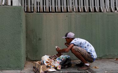 Građanin Venecuele jede hranu koju je pronašao u Kontejneru