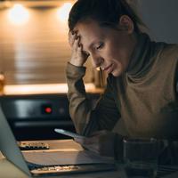 Žena gleda u telefon i kompjuter