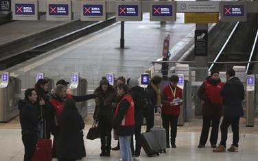 Željeznička stanica u Parizu: Radnici stanice u crvenim jaknama razgovaraju sa putnicima