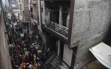 Ljudi se okupljaju oko skladišta gdje je u ranim satima ponedeljka izbio požar u oblasti Kirari u Nju Delhiju