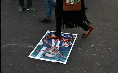 Demonstrant gazi poster sa likom Asada al Ejdanija
