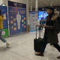 Putnici prolaze pored punkta na kojem im se provjerava zdravstveno stanje: Detalj sa aerodroma u glavnom gradu Kine, Pekingu