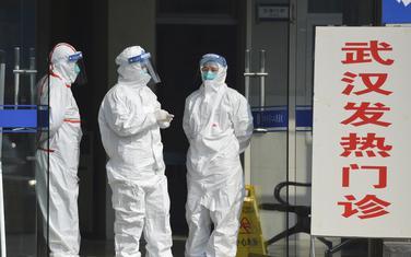 Medicinari u zaštitnim odjelima na ulazu klinike za zaražene pacijente u Vuhanu